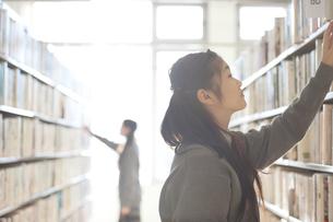 図書館で本を選ぶ中学生の写真素材 [FYI04560291]