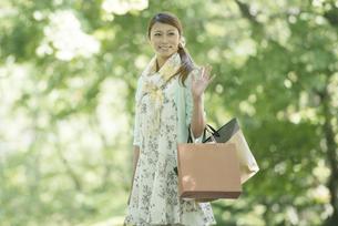 ショッピングバッグを持ち微笑む女性の写真素材 [FYI04560351]