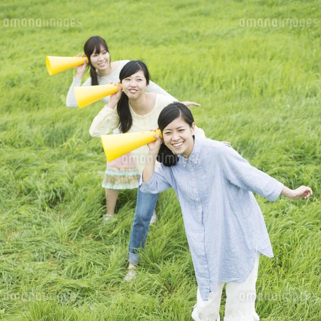草原でメガホンを持ち微笑む3人の女性の写真素材 [FYI04560368]