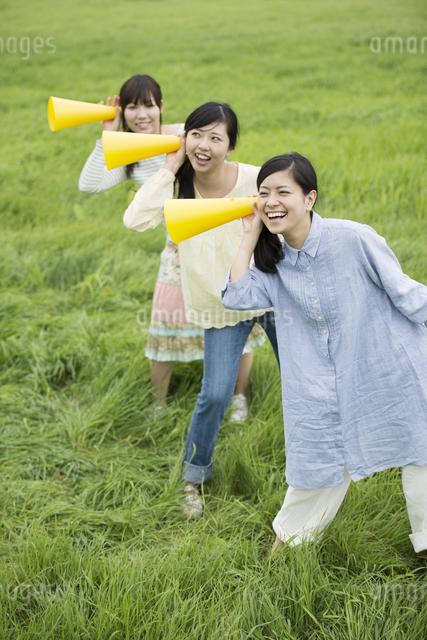 草原でメガホンを持ち微笑む3人の女性の写真素材 [FYI04560369]