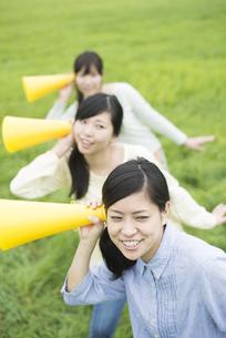 草原でメガホンを持ち微笑む3人の女性の写真素材 [FYI04560370]