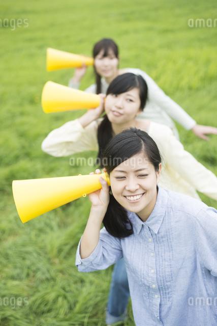 草原でメガホンを持ち微笑む3人の女性の写真素材 [FYI04560371]