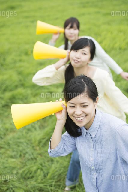 草原でメガホンを持ち微笑む3人の女性の写真素材 [FYI04560372]