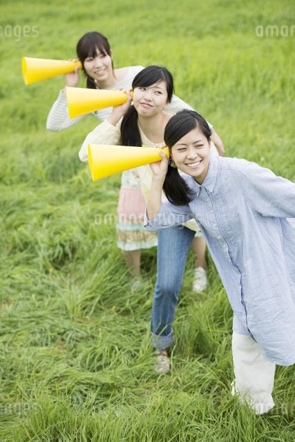 草原でメガホンを持ち微笑む3人の女性の写真素材 [FYI04560374]