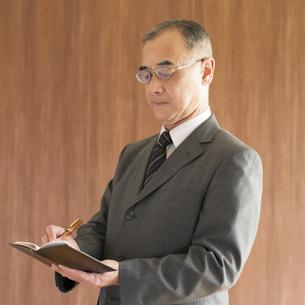 手帳にメモをするビジネスマンの写真素材 [FYI04560391]