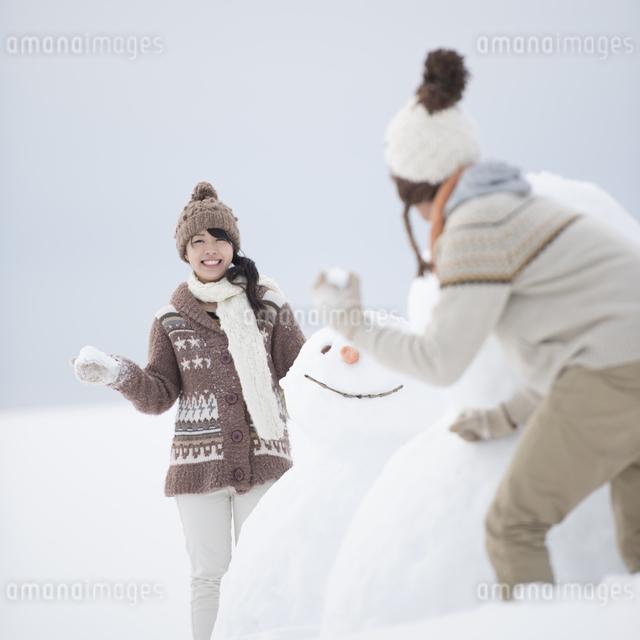 雪だるまの周りで雪合戦をするカップルの写真素材 [FYI04560397]