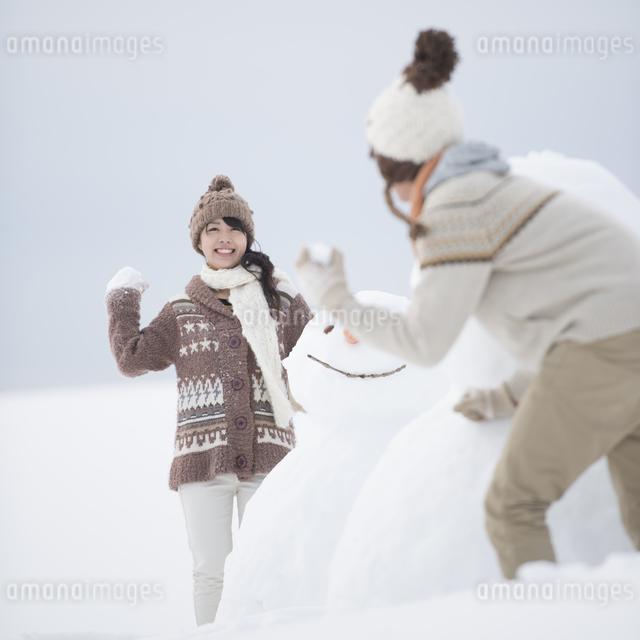 雪だるまの周りで雪合戦をするカップルの写真素材 [FYI04560398]
