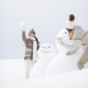 雪だるまの周りで雪合戦をするカップルの写真素材 [FYI04560399]