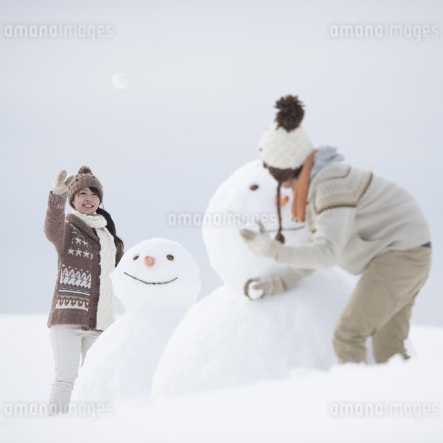 雪だるまの周りで雪合戦をするカップルの写真素材 [FYI04560400]