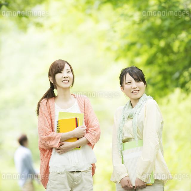 新緑の中で微笑む大学生の写真素材 [FYI04560408]