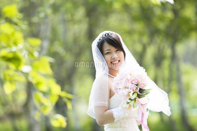ブーケを持ち微笑む花嫁の写真素材 [FYI04560414]