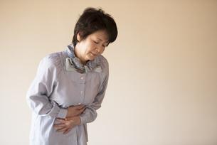 腹痛に悩むシニア女性の写真素材 [FYI04560421]