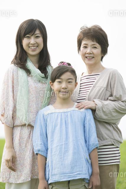 草原で微笑む三世代家族の写真素材 [FYI04560473]