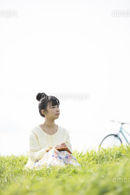 草原で音楽を聴く女性の写真素材 [FYI04560486]