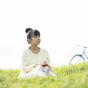 草原で音楽を聴く女性の写真素材 [FYI04560487]