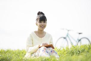 草原で音楽を聴く女性の写真素材 [FYI04560490]
