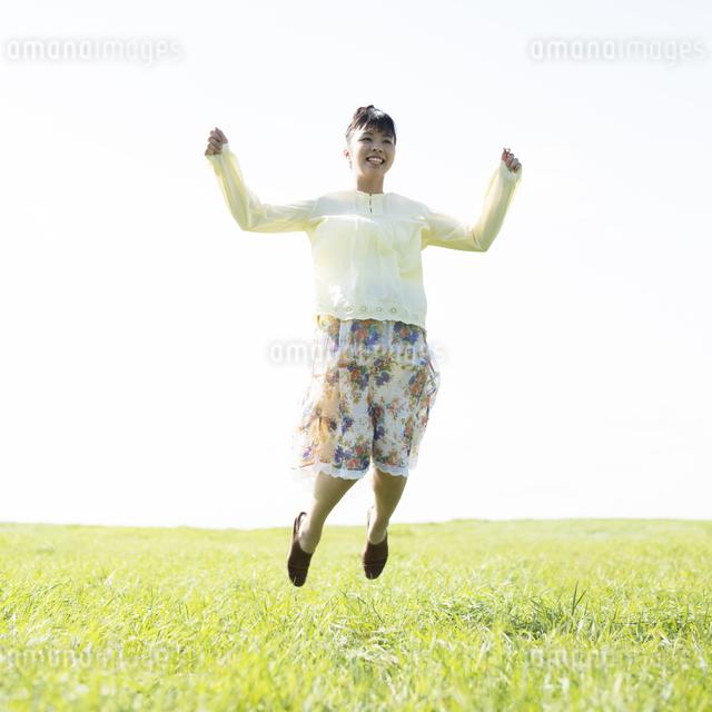 草原でジャンプをする女性の写真素材 [FYI04560495]