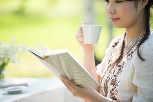 自然の中で読書をする女性の写真素材 [FYI04560508]