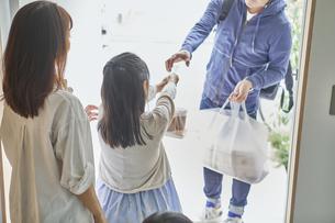 男性のフードデリバリースタッフと受け取る親子の写真素材 [FYI04561589]