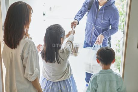 男性のフードデリバリースタッフと受け取る親子の写真素材 [FYI04561590]