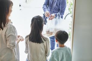 男性のフードデリバリースタッフと受け取る親子の写真素材 [FYI04561610]