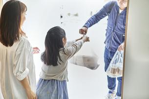 男性のフードデリバリースタッフと受け取る親子の写真素材 [FYI04561611]
