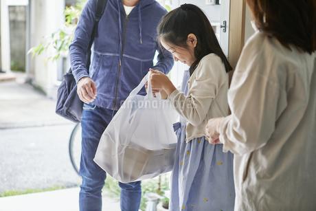 男性のフードデリバリースタッフと受け取る親子の写真素材 [FYI04561613]