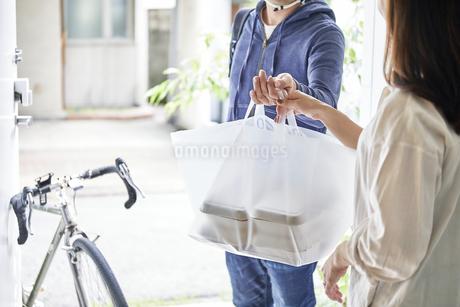 男性のフードデリバリースタッフと受け取る女性の写真素材 [FYI04561620]