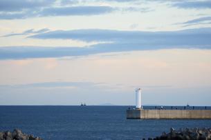 灯台がある堤防で釣りをする人々の写真素材 [FYI04561781]