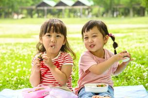 並んでおにぎりを食べる女の子の写真素材 [FYI04563055]