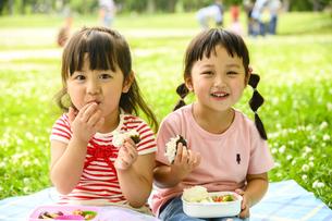 並んでおにぎりを食べる女の子の写真素材 [FYI04563060]