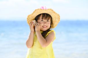 貝殻を耳に当てる女の子の写真素材 [FYI04563154]