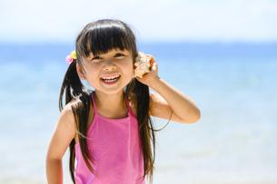貝殻を耳に当てる女の子の写真素材 [FYI04563194]