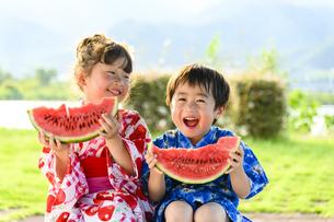 浴衣を着てスイカを食べる女の子と男の子の写真素材 [FYI04563320]
