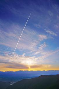 王ヶ鼻から望む松本市街と穂高連峰と飛行機雲と夕日の写真素材 [FYI04563830]