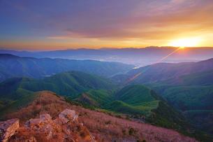 王ヶ鼻から望む松本市街と穂高連峰など北アルプスと夕日の写真素材 [FYI04563836]
