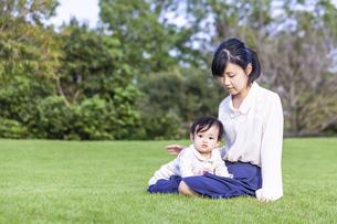 緑の樹木を背景に座り赤ちゃんと遊ぶ若い母の写真素材 [FYI04564109]