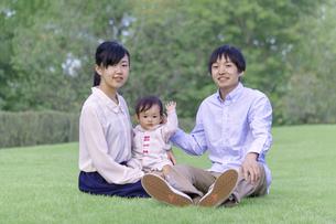 緑の樹木を背景に座り赤ちゃんと遊ぶ若い夫婦の写真素材 [FYI04564117]