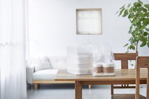 ダイニングテーブルに置かれたフードデリバリーの食事の写真素材 [FYI04564327]