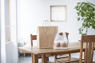ダイニングテーブルに置かれたフードデリバリーの食事の写真素材 [FYI04564328]