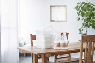 ダイニングテーブルに置かれたフードデリバリーの食事の写真素材 [FYI04564330]