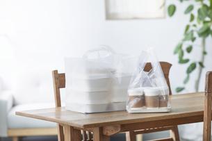 ダイニングテーブルに置かれたフードデリバリーの食事の写真素材 [FYI04564331]