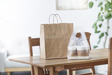 ダイニングテーブルに置かれたフードデリバリーの食事の写真素材 [FYI04564332]