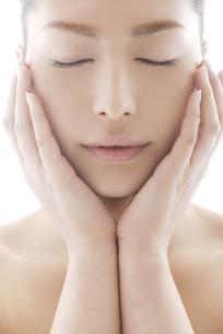 頬に触れる女性のビューティーイメージの写真素材 [FYI04565573]