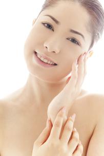 頬を撫でる20代日本人女性のビューティーイメージの写真素材 [FYI04565700]