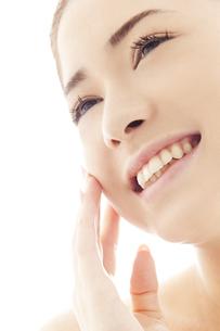 頬を撫でる20代日本人女性のビューティーイメージの写真素材 [FYI04565710]