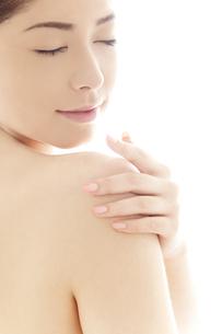 肩を撫でる20代日本人女性のビューティーイメージの写真素材 [FYI04565713]