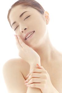 頬を撫でる20代日本人女性のビューティーイメージの写真素材 [FYI04565723]