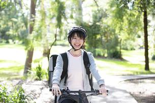 自転車に乗ったフードデリバリーの配達員の女性の写真素材 [FYI04566206]