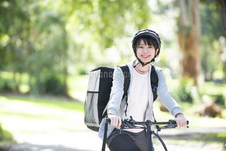 自転車に乗ったフードデリバリーの配達員の女性の写真素材 [FYI04566208]
